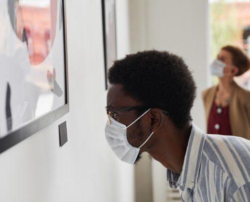 Man Wearing Mask Looking at Modern Art in Museum
